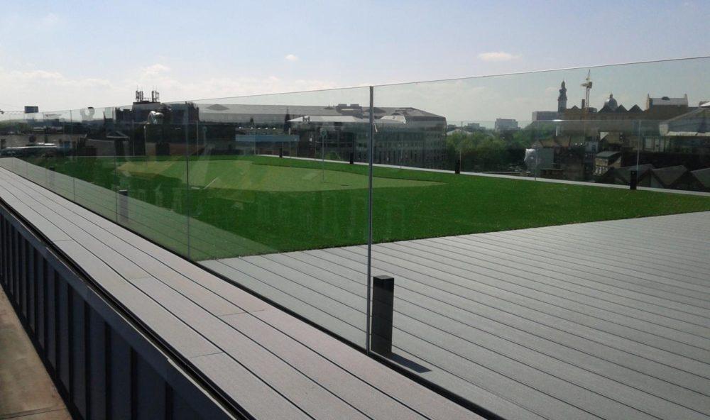 Realisatie in glaswerk: verbouwing van kantoren en lofts in centrum Gent – glazen borstwering rond dakterras met puttinggreen.